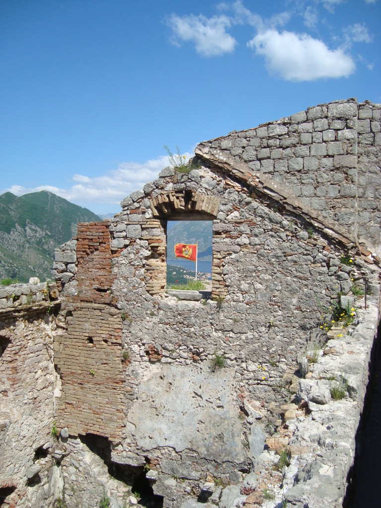 Montenegrin flag through fortress window.